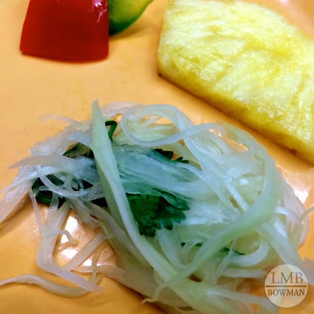 Tasting plate of bell peppers, pineapple and a green papaya salad with cilantro and fish sauce.