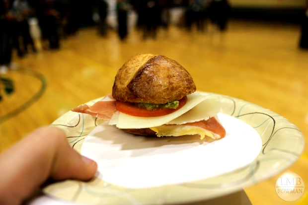 Slider of proscuitto, cheese, tomato and green olive tapenade on a biscuit bun