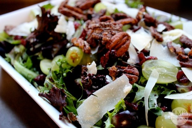 Fall salad with spring greens, grapes, Parmesan cheese, dried cranberries, candied pecans and pomegranate balsamic.