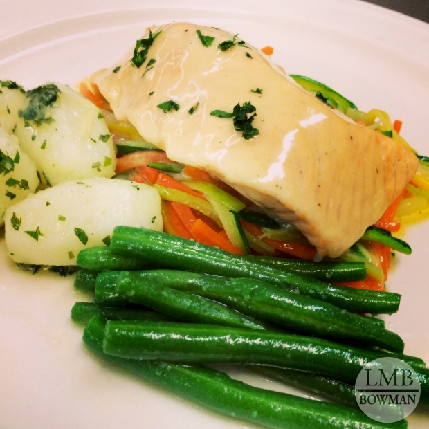 Submerged poached salmon with beurre blanc, sautéed julienned vegetables, tourned potatoes, and buttered green beens.
